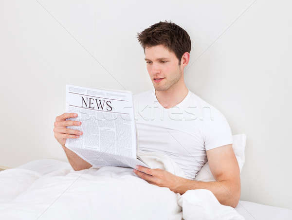 Man lezing krant jonge knappe man bed Stockfoto © AndreyPopov