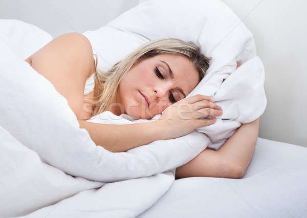 Upset woman lying on bed Stock photo © AndreyPopov