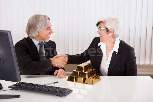Businesswoman with gold bullion bars Stock photo © AndreyPopov