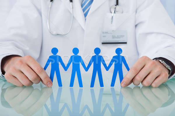 Stock photo: Doctor Holding Blue Paper People Chain At Desk