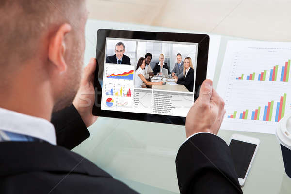 Businessman on a video or conference call on his tablet Stock photo © AndreyPopov