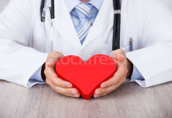 Midsection Of Doctor Holding Red Heart At Desk Stock photo © AndreyPopov