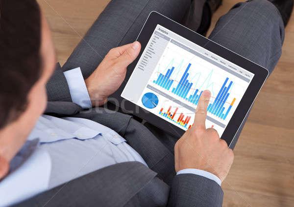Businessman Comparing Graphs On Digital Tablet Stock photo © AndreyPopov