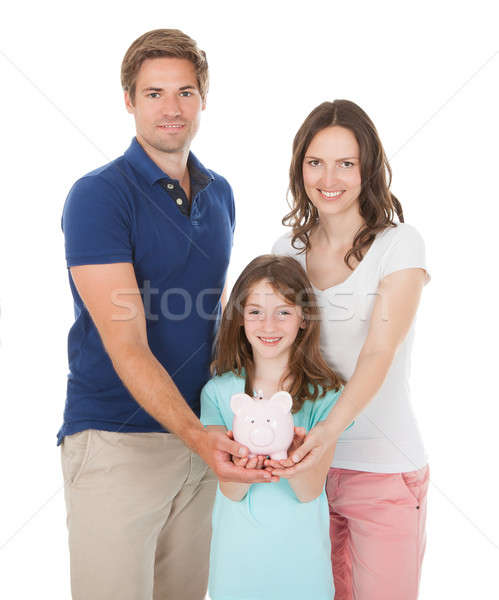 Happy Family Holding Piggy Bank Together Stock photo © AndreyPopov