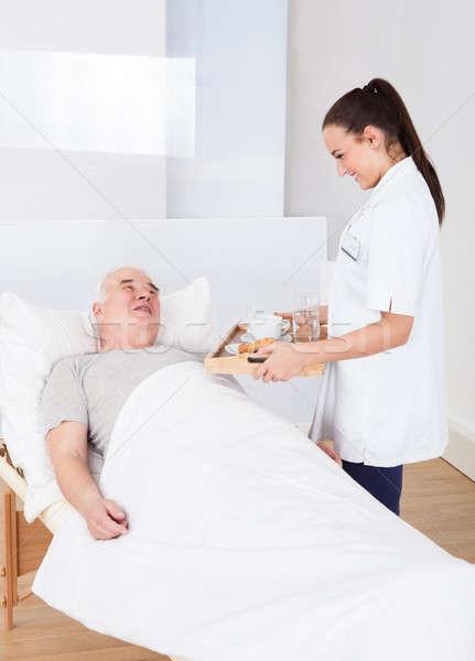 Doctor Serving Breakfast To Senior Man Stock photo © AndreyPopov