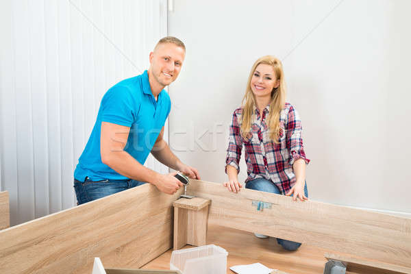 Couple Assembling Wooden Furniture Stock photo © AndreyPopov