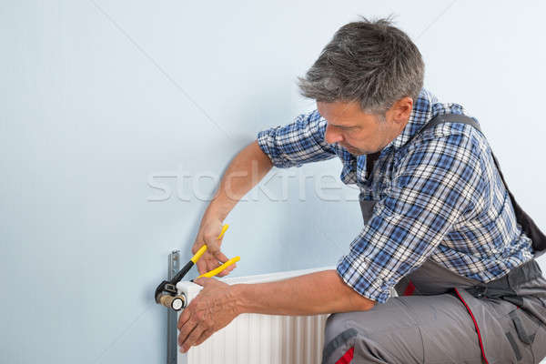 Plumber Fixing Radiator With Wrench Stock photo © AndreyPopov