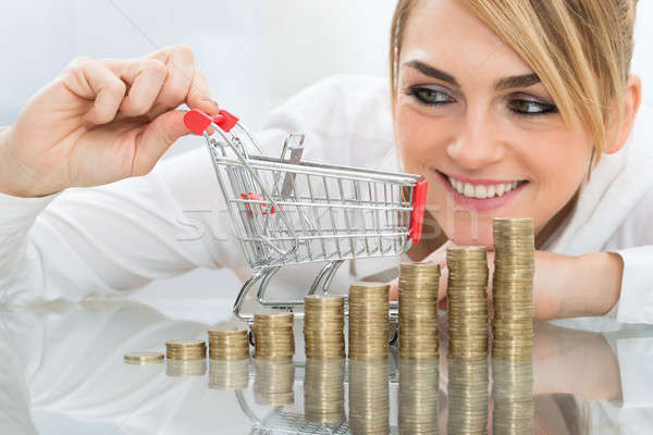 Businesswoman With Mini Shopping Cart And Coins Stock photo © AndreyPopov