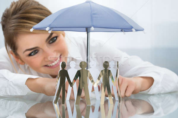 Businesswoman Protecting Cut-out Figures With Umbrella Stock photo © AndreyPopov