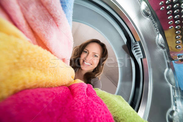 Feliz mulher ver dentro máquina de lavar Foto stock © AndreyPopov