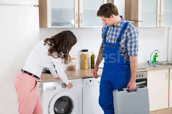 Woman Showing Damage In Washing Machine To Repairman Stock photo © AndreyPopov
