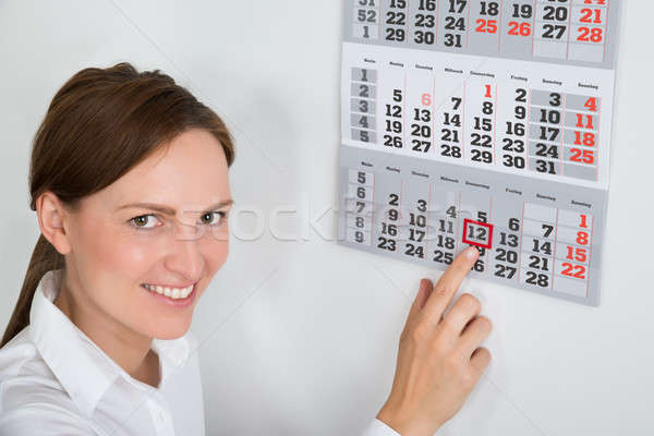 Businesswoman Placing Red Mark On Calendar Date Stock photo © AndreyPopov