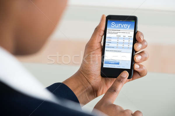 Businesswoman Filling Survey Form On Mobile Phone Stock photo © AndreyPopov