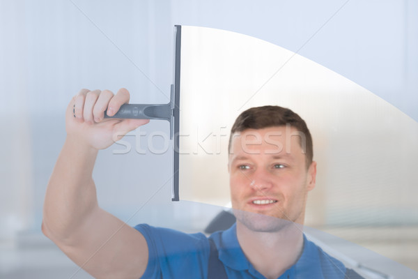 Worker Cleaning Glass Window With Squeegee Stock photo © AndreyPopov