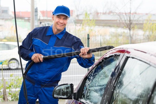 Confident Mature Serviceman Washing Car At Garage Stock photo © AndreyPopov