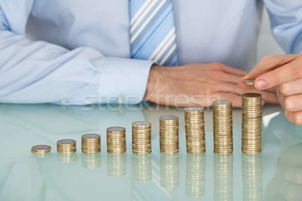 Businessman Making Stack Of Coins Stock photo © AndreyPopov