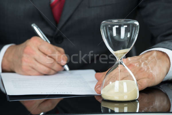 Close-up Of Businessman Filling Form With Hourglass Stock photo © AndreyPopov