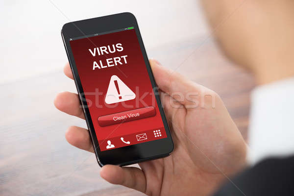 Businessman Holding Mobile Phone With Virus Alert Stock photo © AndreyPopov