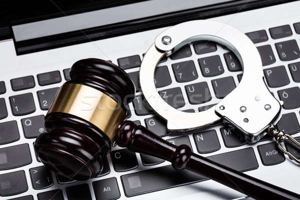 Gavel And Handcuff On Laptop Keyboard Stock photo © AndreyPopov
