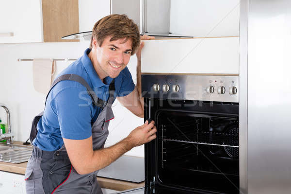 Repairman With Screwdriver Fixing Oven Stock photo © AndreyPopov