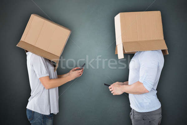 Couple Covering Their Heads With Cardboard box Texting Stock photo © AndreyPopov