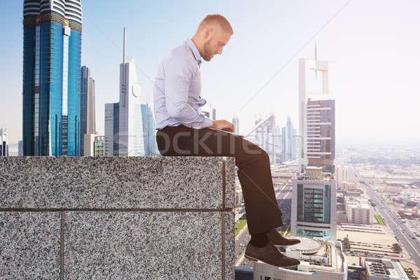 Empresário borda telhado usando laptop jovem sessão Foto stock © AndreyPopov