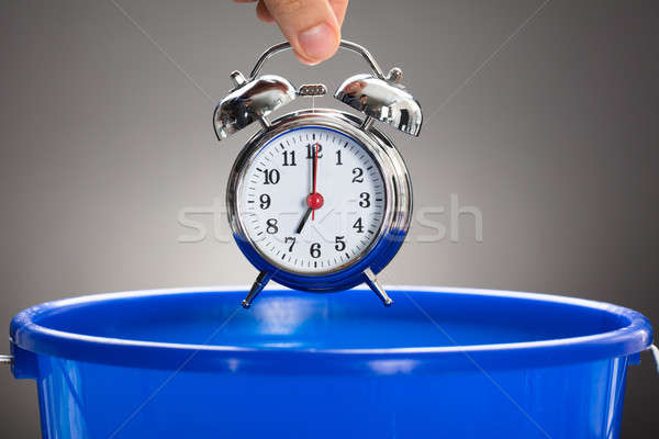 Stock photo: Businessman's Hand Throwing Alarm Clock In Blue Bucket