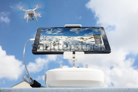 Drone filming cloudy sky seen on digital tablet during sunset Stock photo © AndreyPopov