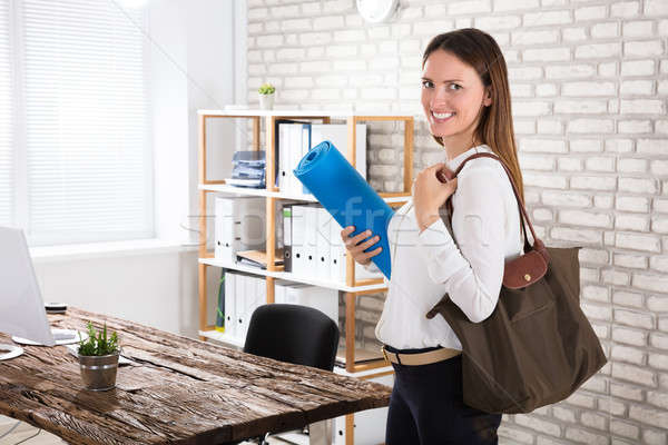 Businesswoman Walking In Office With Exercise Mat Stock photo © AndreyPopov