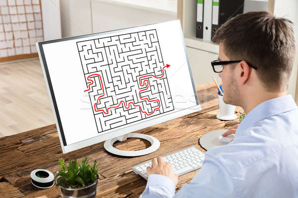 Businessman Solving Maze On Computer Stock photo © AndreyPopov