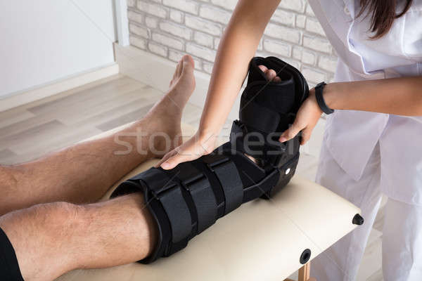 Orthopedist Putting Walking Brace To Patient's Leg Stock photo © AndreyPopov