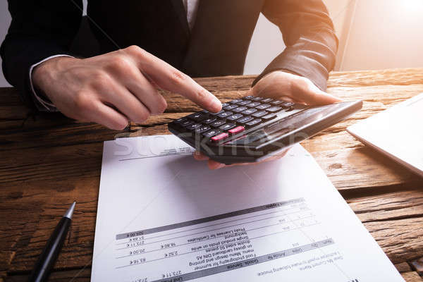 Businessperson Calculating Bill With Calculator Stock photo © AndreyPopov