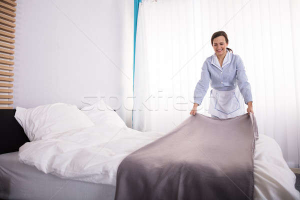 Housekeeper Making Bed In Hotel Room Stock photo © AndreyPopov