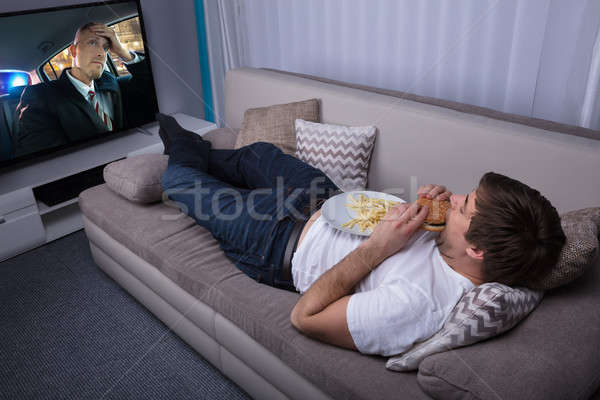 Man eten hamburger jonge man sofa Stockfoto © AndreyPopov