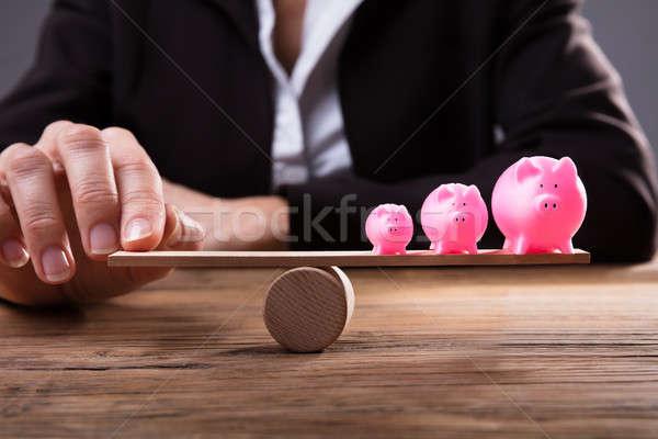 Businessperson's Finger Balancing Piggybanks On Seesaw Stock photo © AndreyPopov