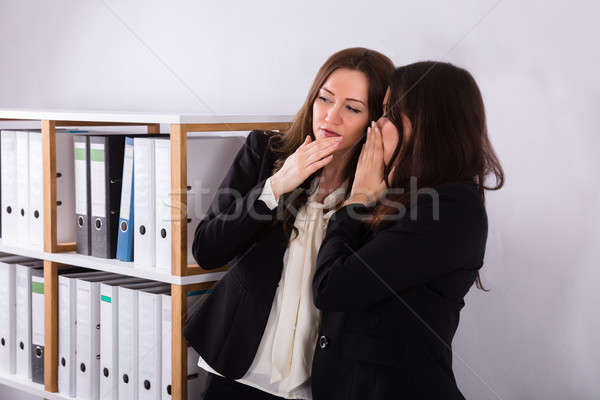 Businesswoman Whispering Into Colleague's Ear Stock photo © AndreyPopov