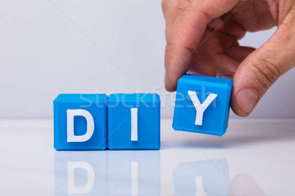 Human Hand Making Word Diy With Blue Cubic Blocks Stock photo © AndreyPopov
