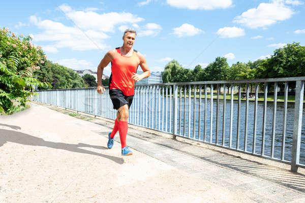 Mature Athletic Man Running On Sidewalk Stock photo © AndreyPopov