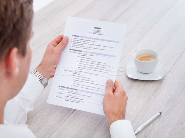 Stock photo: Businessman Reading Resume With Tea Cup On Desk