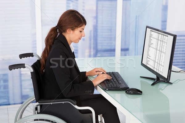 Femme d'affaires séance fauteuil roulant vue de côté portrait Photo stock © AndreyPopov