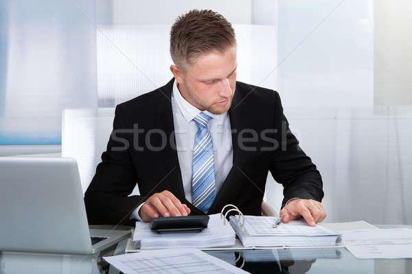 Hardworking businessman analyzing a report Stock photo © AndreyPopov
