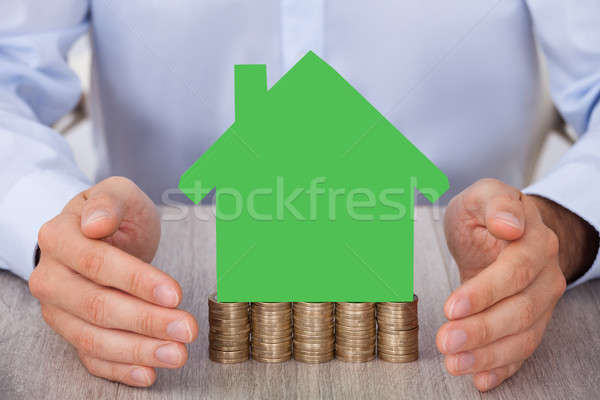 Businessman Protecting Green Model House On Stacked Coins Stock photo © AndreyPopov