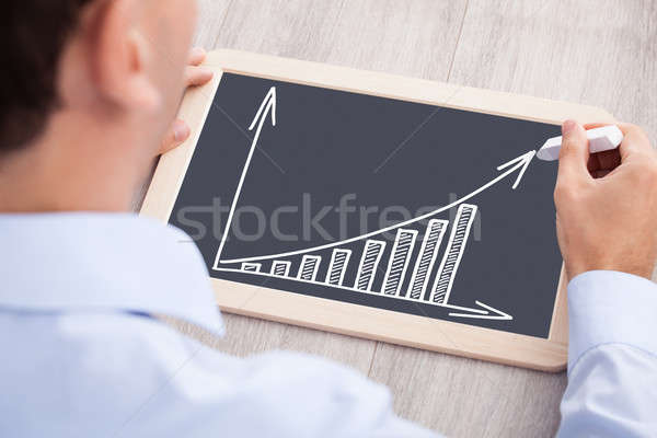 Businessman Drawing Bargraph On Slate At Desk Stock photo © AndreyPopov