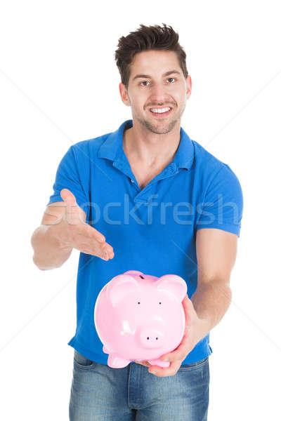 Young Man Holding Piggybank Stock photo © AndreyPopov