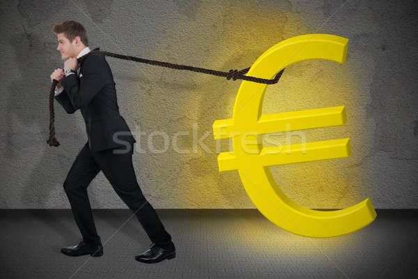 Determined Businessman Pulling Glowing Euro Sign Stock photo © AndreyPopov
