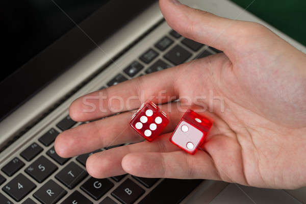Businessman Holding Red Dices While Using Laptop Stock photo © AndreyPopov