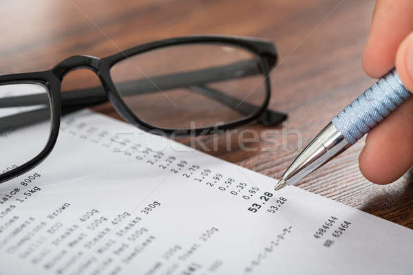 Person Hands With Pen Over Receipt And Eyeglasses Stock photo © AndreyPopov