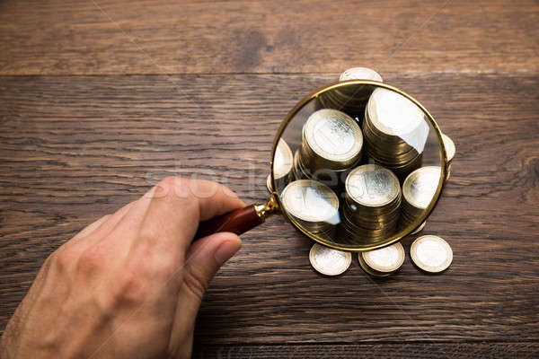 Businessman Holding Magnifying Glass Over Coins Stock photo © AndreyPopov