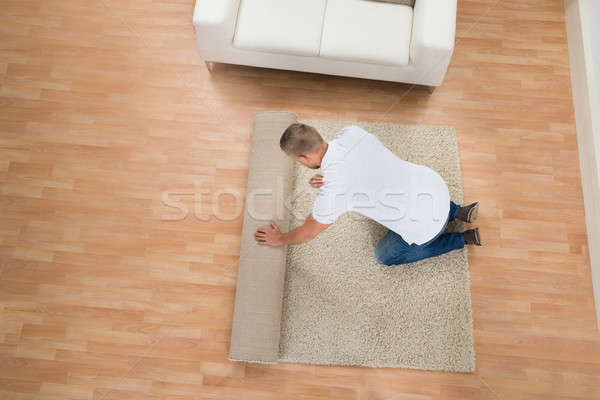 Young Man Unrolling Carpet Stock photo © AndreyPopov