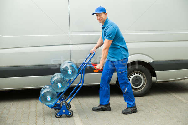 Delivery Man Holding Trolley With Water Bottles Stock photo © AndreyPopov